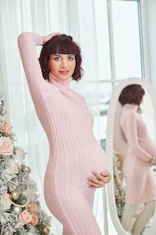 Schwangere frau wartet auf weihnachten nahe dem weihnachtsbaum. schwangerschaft und warten auf die geburt eines kindes
