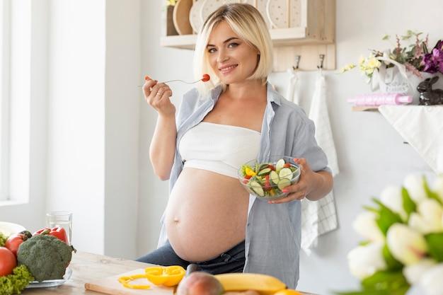 Schwangere frau, welche die kamera in der küche betrachtet