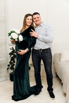 Schwangere frau wird sanft an ihren ehemann gedrückt