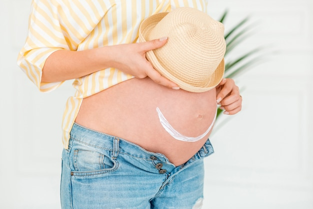 Schwangere frau zeichnet lächeln auf ihrem bauch mit lichtschutz