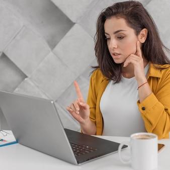 Schwangere frau zeigt einen moment finger zu laptop zu hause