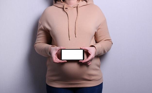 Schwangere frau zeigt handy mit leerem display zu hause, mobile anwendung für schwangerschaft.