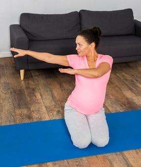 Schwangere frau zu hause, die auf matte trainiert