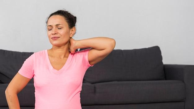 Schwangere frau zu hause, die ihren hals während des trainings hält