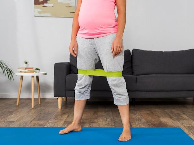 Schwangere frau zu hause, die mit gummiband trainiert