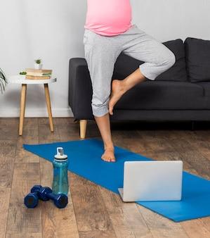 Schwangere frau zu hause, die mit laptop trainiert