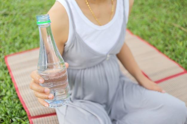 Schwangere frauen haben eine wasserflasche in der hand.
