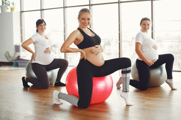 Schwangere frauen machen yoga in einem fitnessstudio