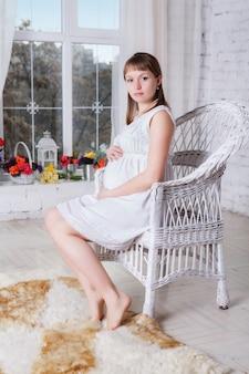 Schwangere frauen sitzen auf einem stuhl, der nahe fenster sich entspannt