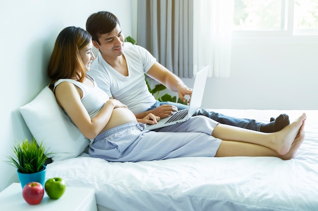 Schwangere frauen und ehemann arbeiten an betten, indem sie ihren laptop für das einkaufen am faulen morgentag verwenden,
