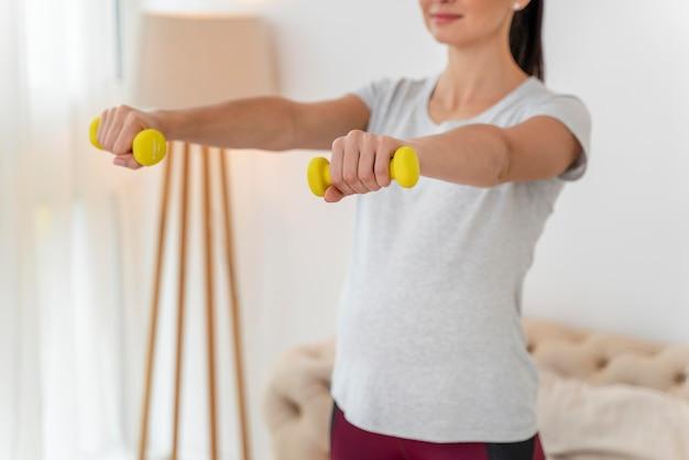 Schwangere frauentraining mit gelben gewichten