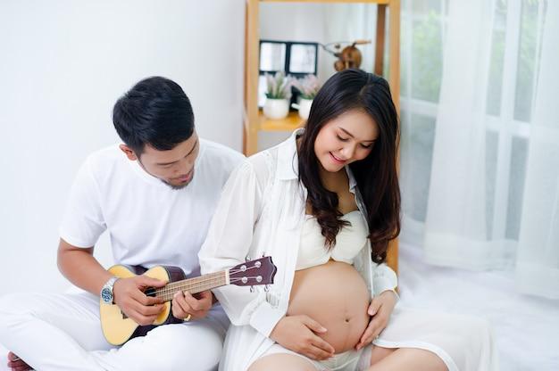 Schwangere genießen ihren ehemann und singen mit liebe lieder für ihre kinder.