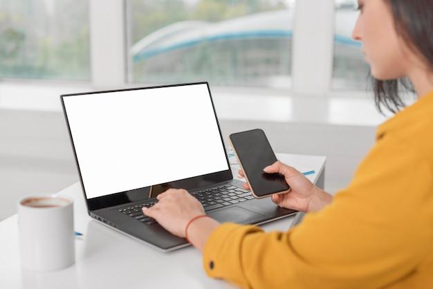 Schwangere geschäftsfrau, die am laptop mit smartphone arbeitet