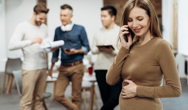 Schwangere geschäftsfrau, die am telefon spricht, während sie ihren bauch berührt