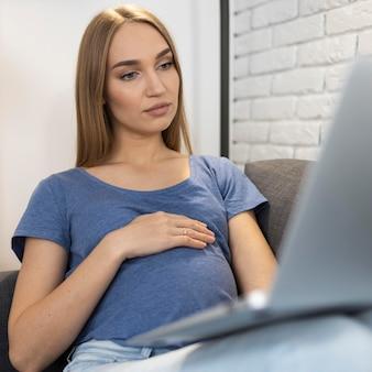 Schwangere geschäftsfrau, die auf der couch sitzt und am laptop arbeitet