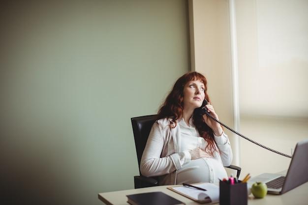Schwangere geschäftsfrau, die ihren bauch berührt, während sie am telefon spricht