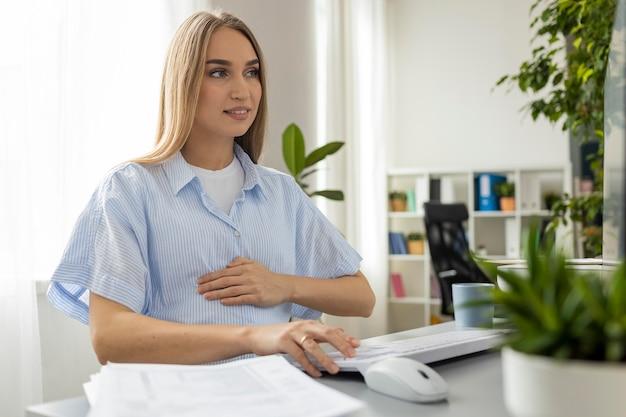 Schwangere geschäftsfrau, die im büro arbeitet