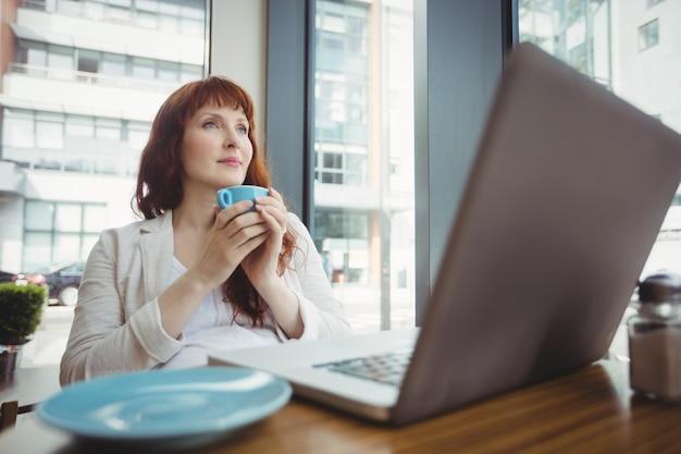 Schwangere geschäftsfrau, die kaffee in der cafeteria trinkt