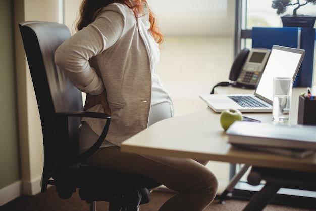Schwangere geschäftsfrau, die sie zurückhält, während sie auf stuhl sitzt