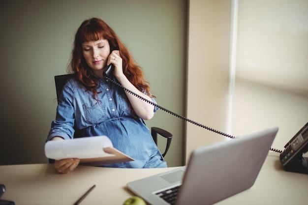Schwangere geschäftsfrau, die während der arbeit am telefon spricht
