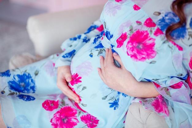Schwangere glückliche frau, die im stuhl sitzt. zimmer in pastellrosa