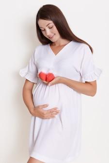 Schwangere glückliche frau, die rote gestrickte babyschuhe in ihren händen hält und ihren bauch mit charmantem lächeln berührt