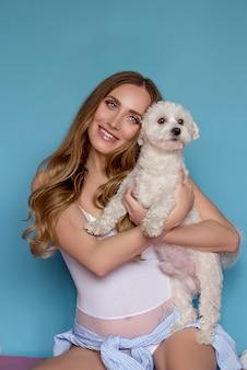 Schwangere glückliche frau mit hund auf blauem hintergrund