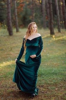 Schwangere glückliche junge frau, die draußen im wald geht