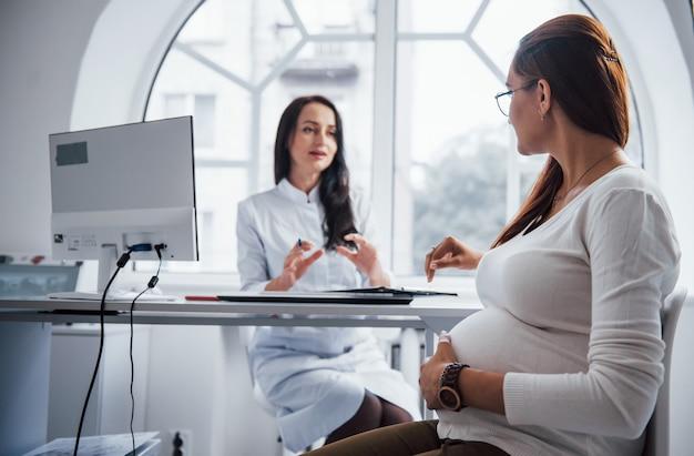 Schwangere haben drinnen rücksprache mit einem geburtshelfer.