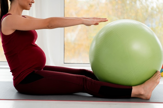 Schwangere junge frau, die mit grünem fitnessball trainiert