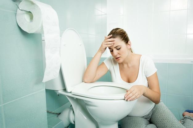 Schwangere junge frau lehnt sich auf toilette und fühlt sich krank