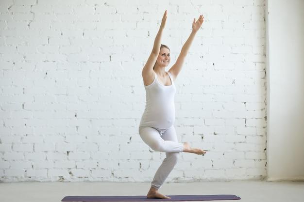 Schwangere junge frau macht pränatale yoga. stuhl pose, utkatasana