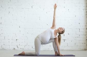 Schwangere junge Frau macht pränatale erweiterte Seitenwinkel Yoga-Pose