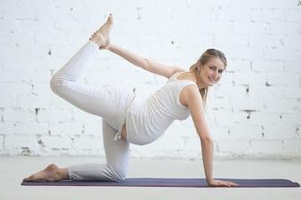 Schwangere junge Frau macht pränatale Sunbird Yoga Pose