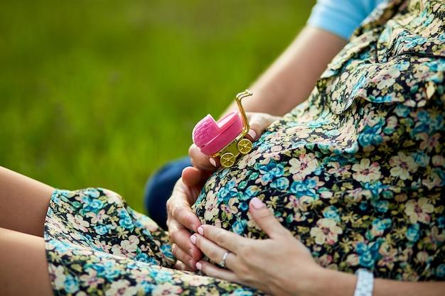 Schwangere junge frau und ein mann, der bauch berührt und wagen hält