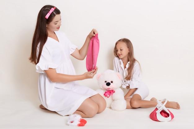 Schwangere junge frau wählt kleidung für ihr baby