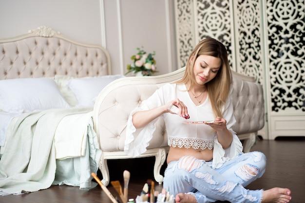 Schwangere junge künstlerin malt bild auf leinwand mit ölfarben in ihrer werkstatt