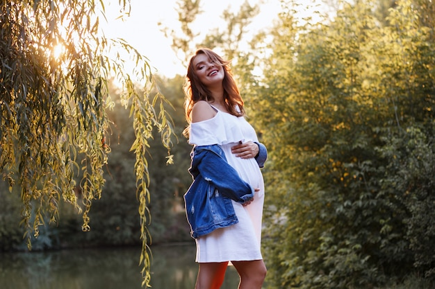 Schwangere junge mutter lacht in die kamera