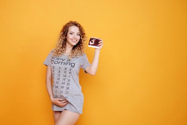 Schwangere junge schöne mode blonde modellfrau im studio hält ultraschalltest auf gelb orange hintergrund