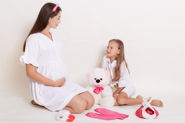 Schwangere junge werdende mutter spielt mit ihrer tochter mit bär