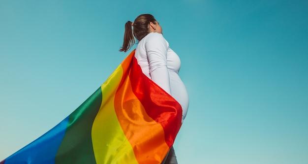 Schwangere lesbenfrau mit einem schwulen stolz, regenbogenfahne, schwangerschafts-lgbtq-konzept