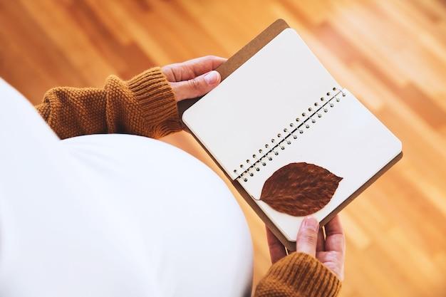 Schwangere macht notizen im notizbuch junge mutter vorfreude auf das baby