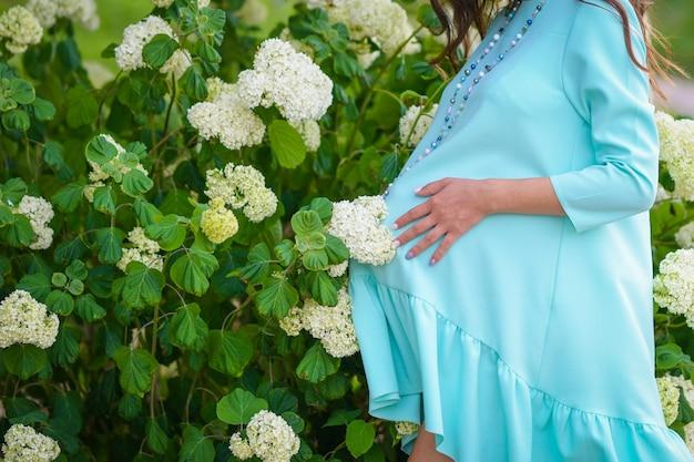 Schwangere mädchen in der nähe von blumen. schöne schwangere frau in einem blauen kleid. schwangerer bauch mit den händen. schwangeres glückliches mädchen in den blumen