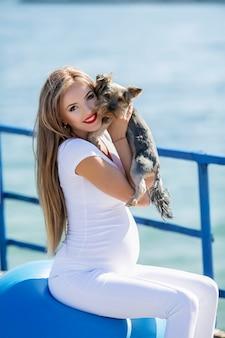 Schwangere mädchen mit spielzeug terrier haustier auf einem spaziergang an einem heißen sommertag