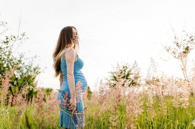 Schwangere mädchen stehen auf gras im freien im gartenhintergrund.