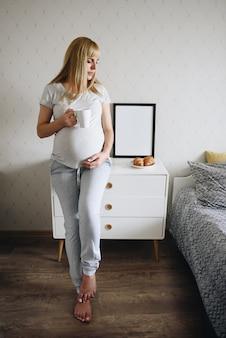 Schwangere mädchenblondine im grauen pyjama. frühstück, kaffee in einer weißen tasse, croissants auf einem teller. weiße kommode.