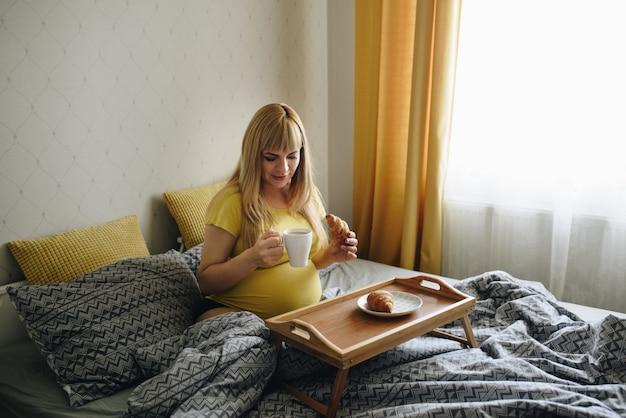 Schwangere mädchenblondine in einem gelben t-shirt zu hause. warten auf ein wunder. schwangerschaft. liebe hoffnung. graue bettwäsche. liegt im bett im schlafzimmer. frühstück im bett. croissants mit kaffee. holztablett.