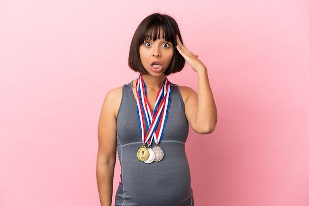 Schwangere mischlingsfrau mit medaillen einzeln auf rosa hintergrund mit überraschungsausdruck