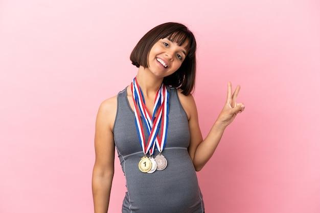 Schwangere mischlingsfrau mit medaillen einzeln auf rosafarbenem hintergrund lächelnd und siegeszeichen zeigend