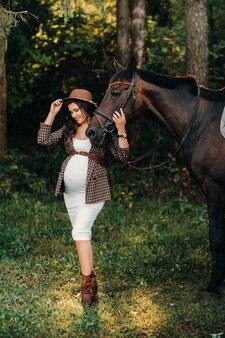 Schwangere mit einem dicken bauch in einem hut neben pferden im wald in der natur. stilvolles mädchen in weißen kleidern und einer braunen jacke.